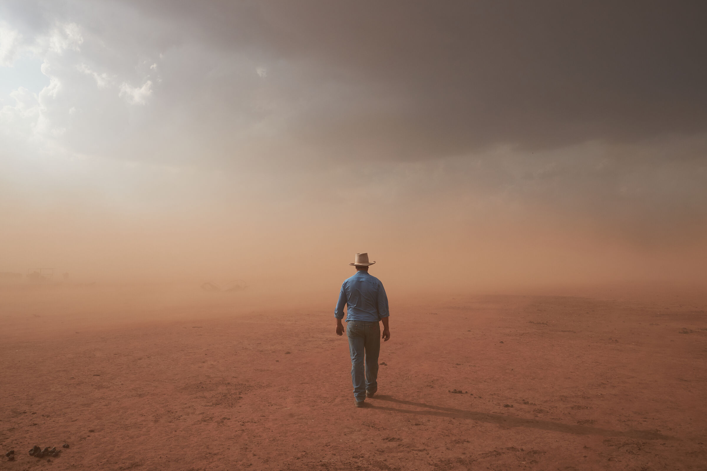 A photograph of a man in a drought afflicted landscape